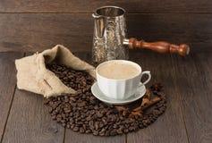 Una taza de café y de granos de café en la tabla de madera Imagen de archivo libre de regalías