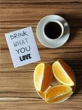 Una taza de café y de naranja en la placa en fondo de madera del zebrano Bebida de la inscripción qué usted ama Foto de archivo