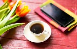 Una taza de café y de tulipanes fotos de archivo