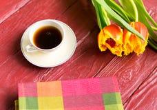 Una taza de café y de tulipanes foto de archivo libre de regalías