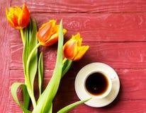 Una taza de café y de tulipanes en un fondo de madera fotografía de archivo libre de regalías