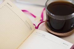 Una taza de café y de un cuaderno en su mesa imágenes de archivo libres de regalías