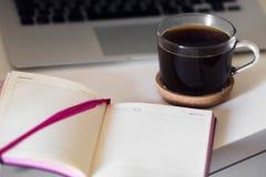 Una taza de café y de un cuaderno en su mesa imagen de archivo libre de regalías