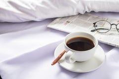Una taza de café y de un periódico en una cama blanca por la mañana foto de archivo