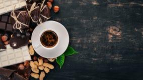 Una taza de café y un sistema de chocolate con las galletas y los dulces En un fondo de madera negro Fotografía de archivo