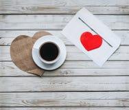 Una taza de café y un sobre con una letra del amor Copie el espacio Fotos de archivo libres de regalías