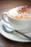 Una taza de Cappuccino con una cuchara Imagen de archivo libre de regalías