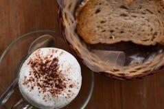 Una taza de capuchino y de pan calientes Imágenes de archivo libres de regalías