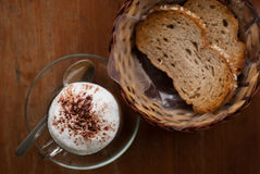 Una taza de capuchino y de pan calientes Foto de archivo libre de regalías