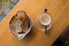 Una taza de capuchino y de pan calientes Fotografía de archivo