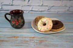Una taza de cer?mica con t? y una placa blanca de la porcelana con los anillos de espuma en la formaci?n de hielo Primer fotografía de archivo