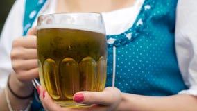 Una taza de una cerveza en una mano más oktoberfest imagen de archivo