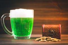 Una taza de cerveza verde en la tabla Hojas del trébol blanco Pecho del oro, pila de las monedas Día de s de StPatrick ' fotos de archivo libres de regalías