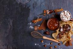 Una taza de chocolate derretido con las avellanas y una taza de melcocha en chocolate Imagen de archivo libre de regalías