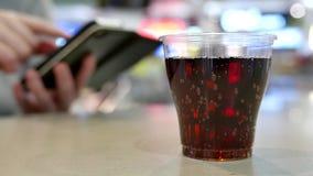 Una taza de Coca-Cola en la tabla con el mensaje de la lectura de la mujer en iphone en la zona de restaurantes almacen de metraje de vídeo