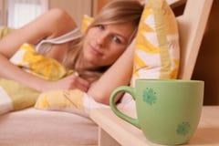 Una taza de cofee en el dormitorio, en mujer del fondo Fotos de archivo libres de regalías