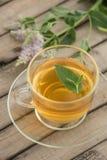 Una taza de cristal con té de oro con los soportes de las hojas y de flores de la menta en un platillo y en una tabla de madera e Fotografía de archivo libre de regalías