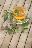 Una taza de cristal con té de oro con los soportes de las hojas y de flores de la menta en un platillo y en una tabla de madera e Imágenes de archivo libres de regalías