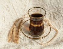 Una taza de cristal de té negro, un collar de la perla y varios oídos maduros del trigo en un cordón poner crema emergen Foto de archivo libre de regalías
