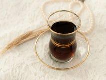 Una taza de cristal de té negro, un collar de la perla y varios oídos maduros del trigo en un cordón poner crema emergen Imagenes de archivo