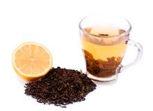 Una taza de cristal hermosa llena de té verde Una taza de té al lado del limón cortado y un montón de hojas de té, aislado en un  Foto de archivo