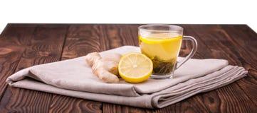 Una taza de cristal llena de té del limón Una taza en una tabla de madera oscura Una taza hermosa con el limón cortado y la raíz  Imágenes de archivo libres de regalías