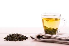 Una taza de cristal llena de té verde Una taza en una tabla de madera ligera Una taza hermosa con el limón y las hojas de té verd Imagen de archivo