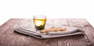 Una taza de cristal llena de té verde Una taza en una tabla de madera Una taza hermosa con el jengibre en un mantel beige, aislad Imagen de archivo