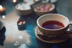 Una taza de cubos rojos del t? y del az?car con diversos gustos, hecha a mano, en la tabla de cristal, ceremonia de t? del este o fotografía de archivo libre de regalías