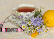 Una taza de flores amarillas y azules del té, del verano del campo, un limón y un collar en un cordón elegante emerge Fotos de archivo libres de regalías