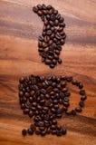 Una taza de granos de café en el fondo de madera fotos de archivo