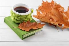 Una taza de hojas del café y del amarillo y de un cuaderno El concepto de otoño, aún vida, relajación, estudio imagen de archivo