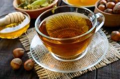 Una taza de infusión de hierbas fragante fresca con la miel y las avellanas en un fondo de madera oscuro Imagenes de archivo