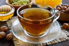 Una taza de infusión de hierbas fragante fresca con la miel y las avellanas en un fondo de madera oscuro Foto de archivo libre de regalías
