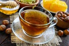 Una taza de infusión de hierbas fragante fresca con la miel y las avellanas en un fondo de madera oscuro Fotografía de archivo libre de regalías