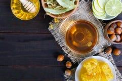 Una taza de infusión de hierbas, miel, panal, avellanas en un fondo de madera oscuro Fotos de archivo