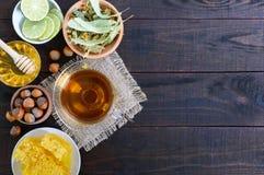 Una taza de infusión de hierbas, miel, panal, avellanas en un fondo de madera oscuro Fotografía de archivo