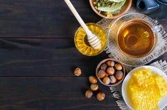 Una taza de infusión de hierbas, miel, panal, avellanas en un fondo de madera oscuro Alimentos sanos Imagen de archivo libre de regalías