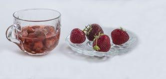 Una taza de jus de las fresas, cuatro fresas Imagen de archivo libre de regalías