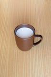 Una taza de la taza que contiene una leche blanca caliente en la tabla de madera Fotografía de archivo libre de regalías