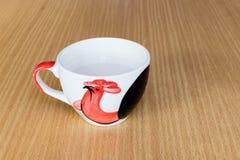 Una taza de la teja que contiene una leche blanca caliente en la tabla de madera Fotografía de archivo