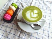 Una taza de latte caliente del matcha tan delicioso con los macarrones Fotos de archivo libres de regalías