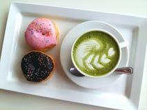 Una taza de latte caliente y de buñuelo del matcha tan deliciosos en blanco Foto de archivo libre de regalías