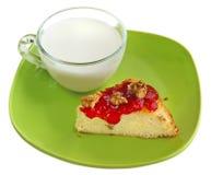 Una taza de leche con el pastel de queso Foto de archivo