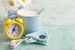 Una taza de leche con la paja, los auriculares y el tenedor Imagen de archivo