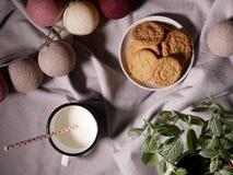 Una taza de leche con una paja dentro En las tortas del fondo Imagen de archivo libre de regalías