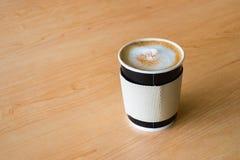 Una taza de papel que contiene un café caliente en la tabla de madera Fotografía de archivo libre de regalías