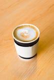 Una taza de papel que contiene un café caliente en la tabla de madera Imágenes de archivo libres de regalías