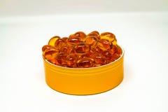 Una taza de suplementos amarillos del softgel Imagen de archivo libre de regalías