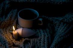 Una taza de té, de una bombilla y de una vela foto de archivo